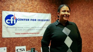 Photo of Debbie Goddard standing in front of Center for Inquiry banner